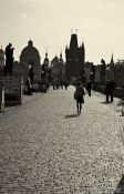 Travel photography:People on Charles Bridge with the Old Town skyline (with a dark yellow tint), Czech Republic