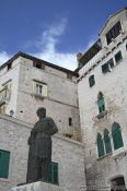 Travel photography:Houses in Sibenik with the bronze statue of Dalmatinac by Ivan Mestrovic, Croatia