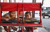 Travel photography:Two boys playing on a cycle rickshaw in Cienfuegos, Cuba
