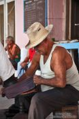 Travel photography:Man polishing shoes in Sancti-Spiritus, Cuba