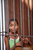 Travel photography:Trinidad girl behind window bars, Cuba
