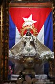Travel photography:Maria statue with Cuban flag inside the Parroquia de San Juan Bautista de Remedios, Cuba