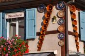 Travel photography:Gugelhupf (ring cake) baking forms on a facade in Obernai, France