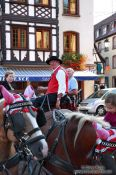 Travel photography:Man in traditional dress on a horse cart in Obernai, France