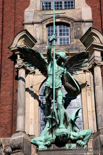 Bronze sculpture of the archangel Michael defeating the devil above the entrance portal of St. Michaelis church (Michel)