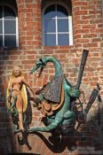 Travel photography:Dragon with maiden decorating a facade in Lübeck, Germany