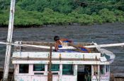 Travel photography:Having a nap on his boat at Elephanta Island near Mumbai, India