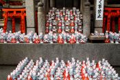 Travel photography:Small figurines of foxes at Kyoto´s Inari shrine, Japan