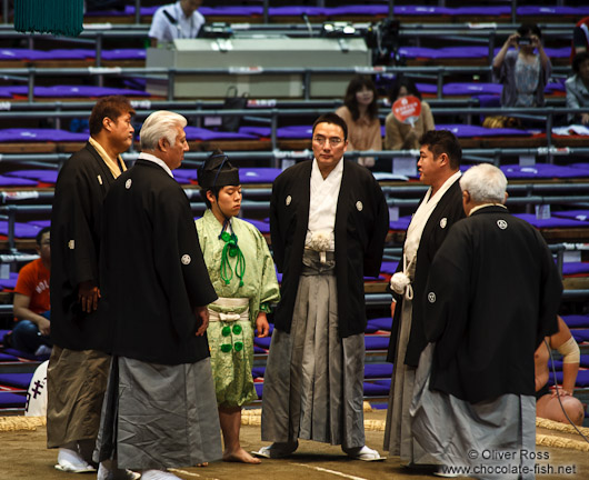 The five shimpan (judges) usually seated around the ring meet in the center to hold a mono-ii at the Nagoya Sumo Tournament