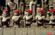 Travel photography:Statues with hats outside a forest shrine, Japan