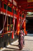 Travel photography:Two girls in kimonos pray at Kyoto´s Inari shrine, Japan