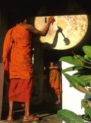 Travel photography:Buddhist monk novice performing the drumming ritual just before sunset, Laos