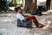 Travel photography:Chichen Itza man sitting in box, Mexico