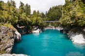 Travel photography:A swimmer jumps into the turquoise glacier water in Hokitika Gorge, New Zealand