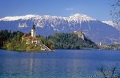 Travel photography:Island with church and Bled Castle with Blejsko jezero (Bled lake) and the Slovenian Alps in the background, Slovenia