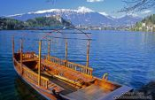 Travel photography:Boat in Blejsko jezero (Bled lake) with Bled Castle in the background, Slovenia