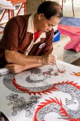 Travel photography:Man painting a cover at the Bo Sang parasol factory, Thailand
