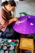 Travel photography:Woman painting a parasol at the Bo Sang parasol factory, Thailand