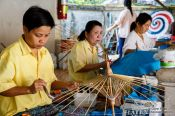 Travel photography:Women assembling the wooden parasols at the Bo Sang parasol factory, Thailand