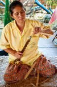 Travel photography:Woman using a hand drill at the Bo Sang parasol factory, Thailand