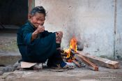 Travel photography:Hmong woman with small fire in a Sapa back yard, Vietnam