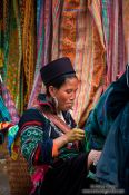 Travel photography:Hmong woman in front of her handy work in Sapa, Vietnam
